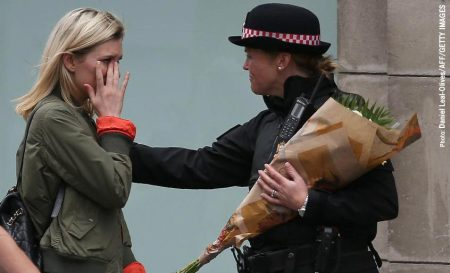 A woman reacts after asking a Police officer to lay flowers near London Bridge as a tribute to the victims of the attack.